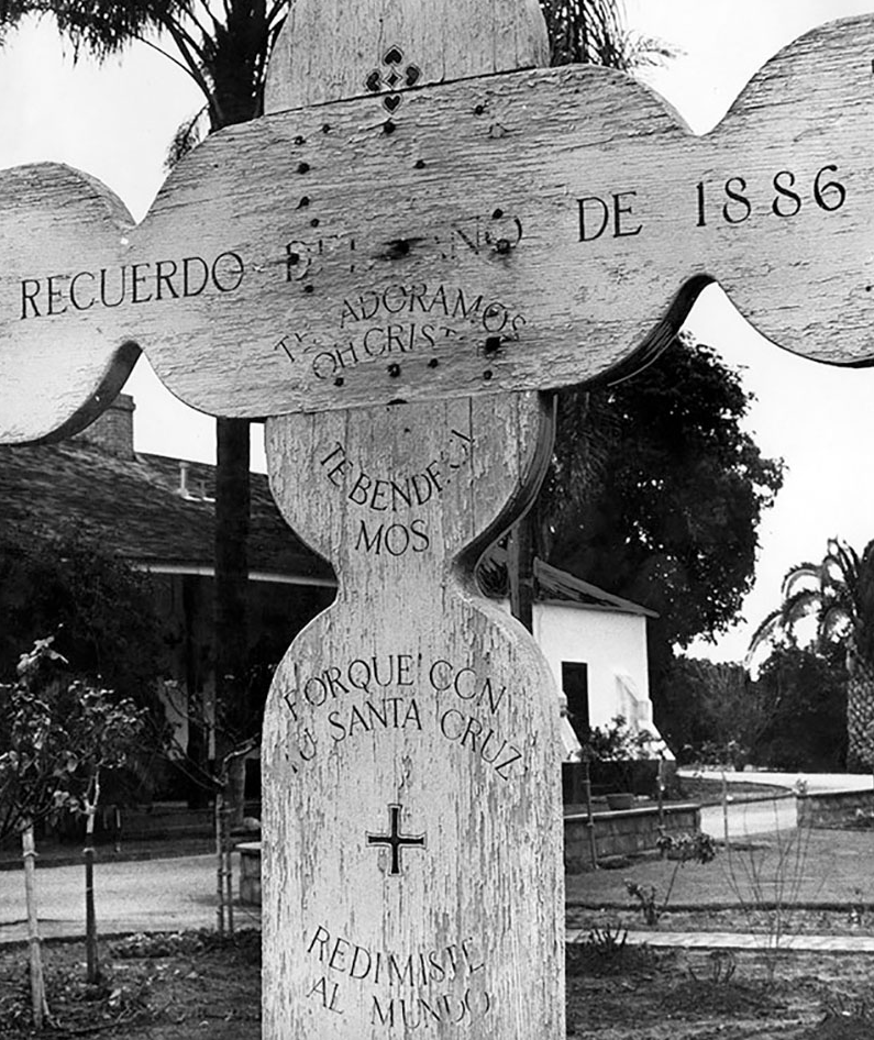"Original wooden cross from the Del Valle family's chapel garden at Rancho Camulos. The English translation of the inscription reads: ""In memory of the year 1886 we adore you, oh Christ, we bless you. Because with your holy cross you redeemed the world."""