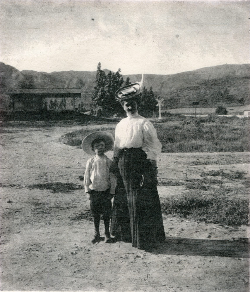 Unidentified woman and boy with the Camulos depot in the background, circa 1906. The depot was built by the Southern Pacific Railroad sometime around the turn of the 20th Century on the Del Valles' Rancho Camulos property, just east of the old ranch buildings and north of the highway.